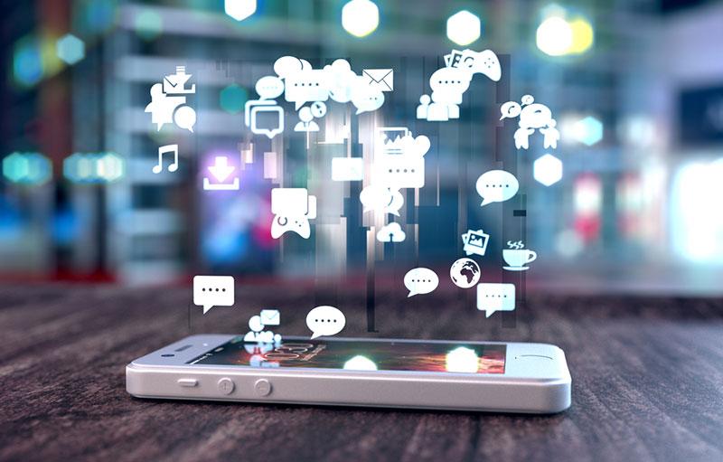 Smartphone blanc sur une table en bois émettant des icônes de réseaux sociaux